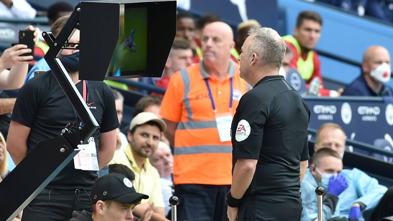 Referee Jon Moss goes to the pitchside monitor to review a Kyle Walker challenge, before overturning his decision to send off the Man City defender and award Southampton a penalty